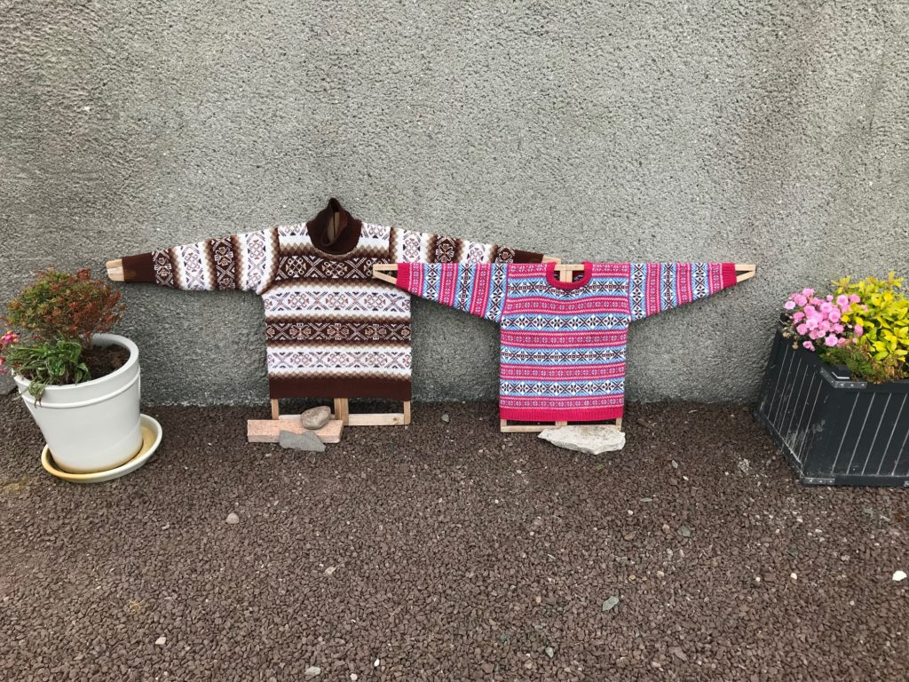Two fair-isle sweaters on traditional Shetland jumper boards leaning against the outside wall of the Shetland Textile Museum.