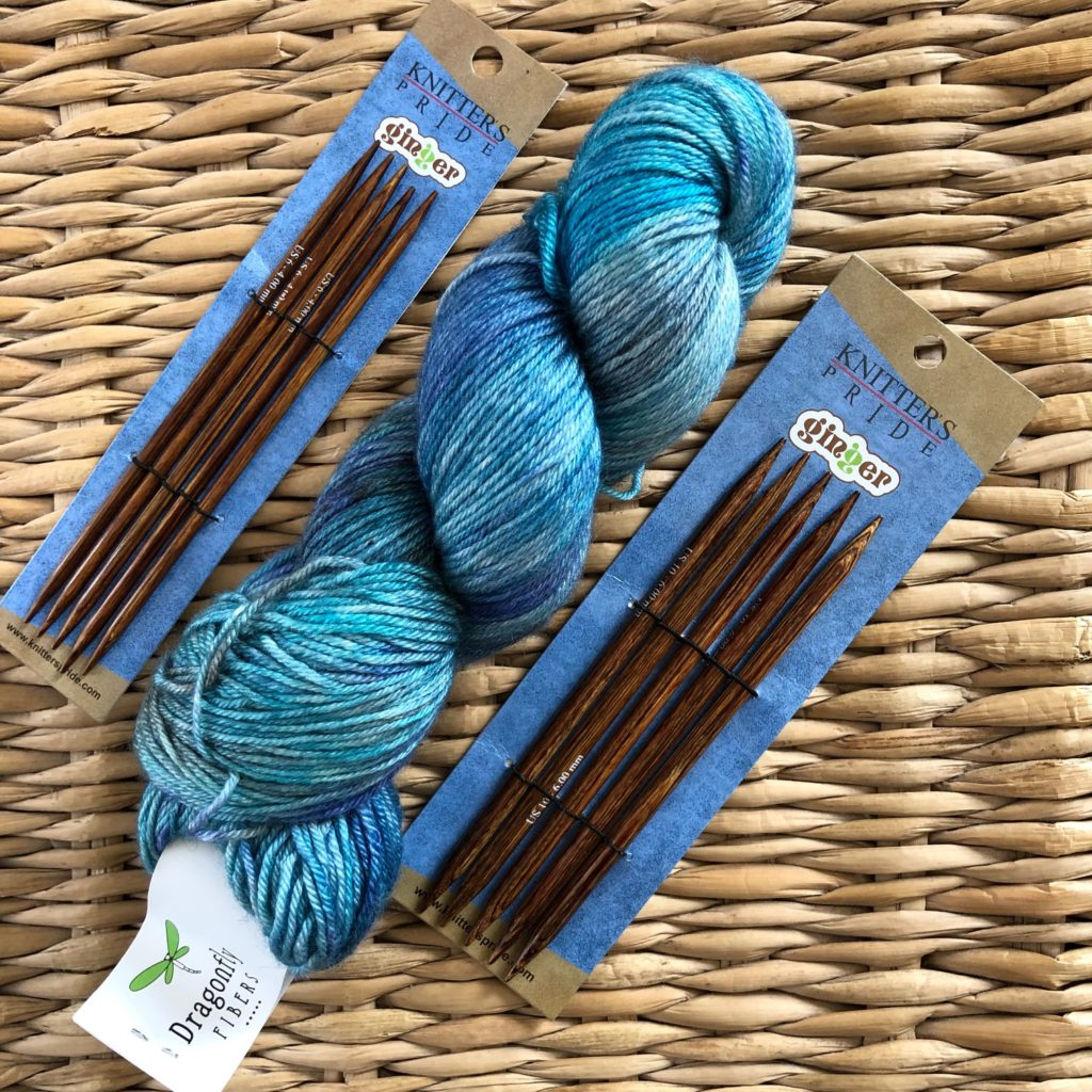 A hank of Selkie Sport in blues and two sets of Knitter's Pride dpns.