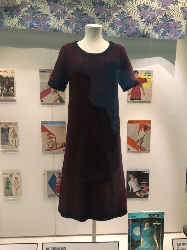 A maroon and black dress knit from a Mary Quant knitting pattern on display at the Victoria and Albert Museum, with knitting and sewing patterns hung in columns on either side.