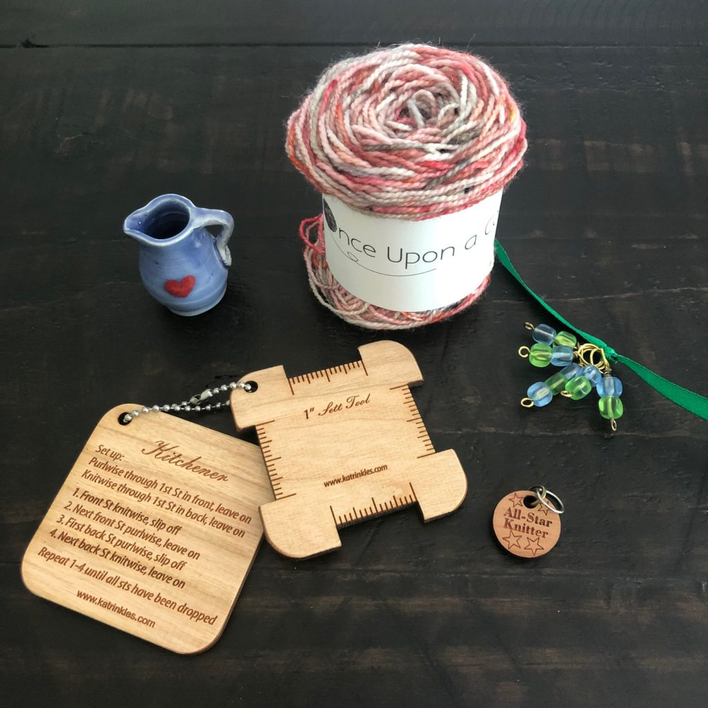 A photo of a small ball of pink, white, and gray yarn, a miniature blue pitcher with a heart on it, a set of blue and green glass stitch markers, a wooden stitch marker and two wooden knitting tools.