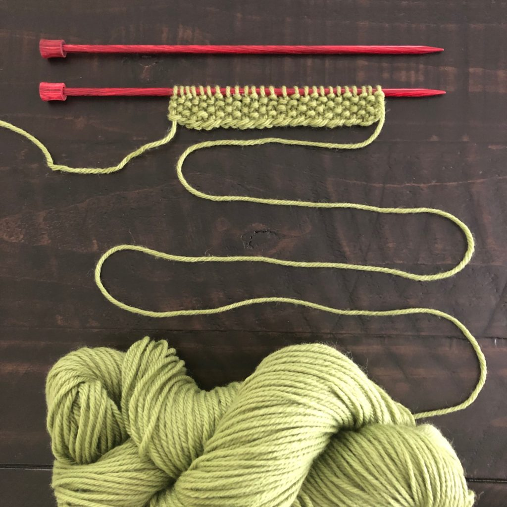 Green Cascade 220 knit up on red Knitter's Pride knitting needles in seed stitch.