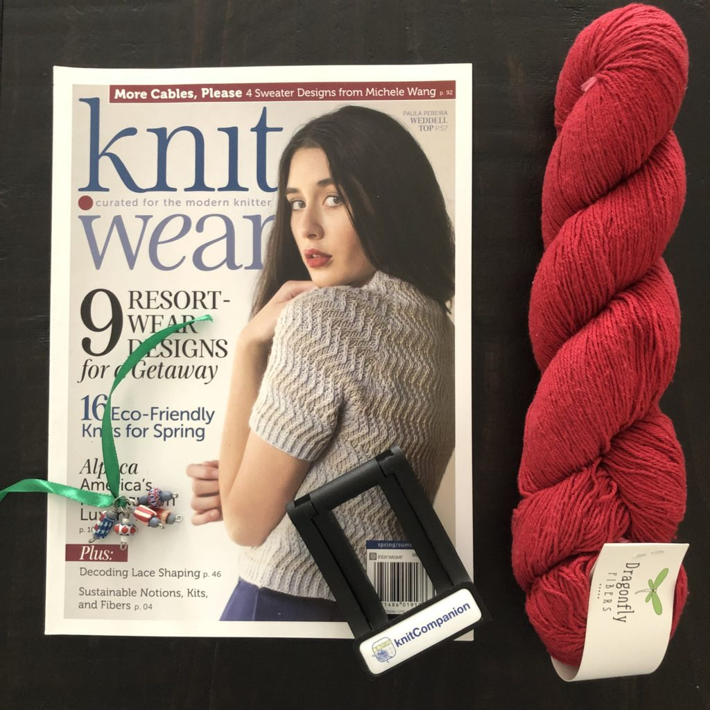 Knitwear magazine Spring/Summer 2018, a knitConmpanion device stand, stitch markers and a hank of Dragonfly Fibers Dance Rustic Silk in the Dragonberry colorway.