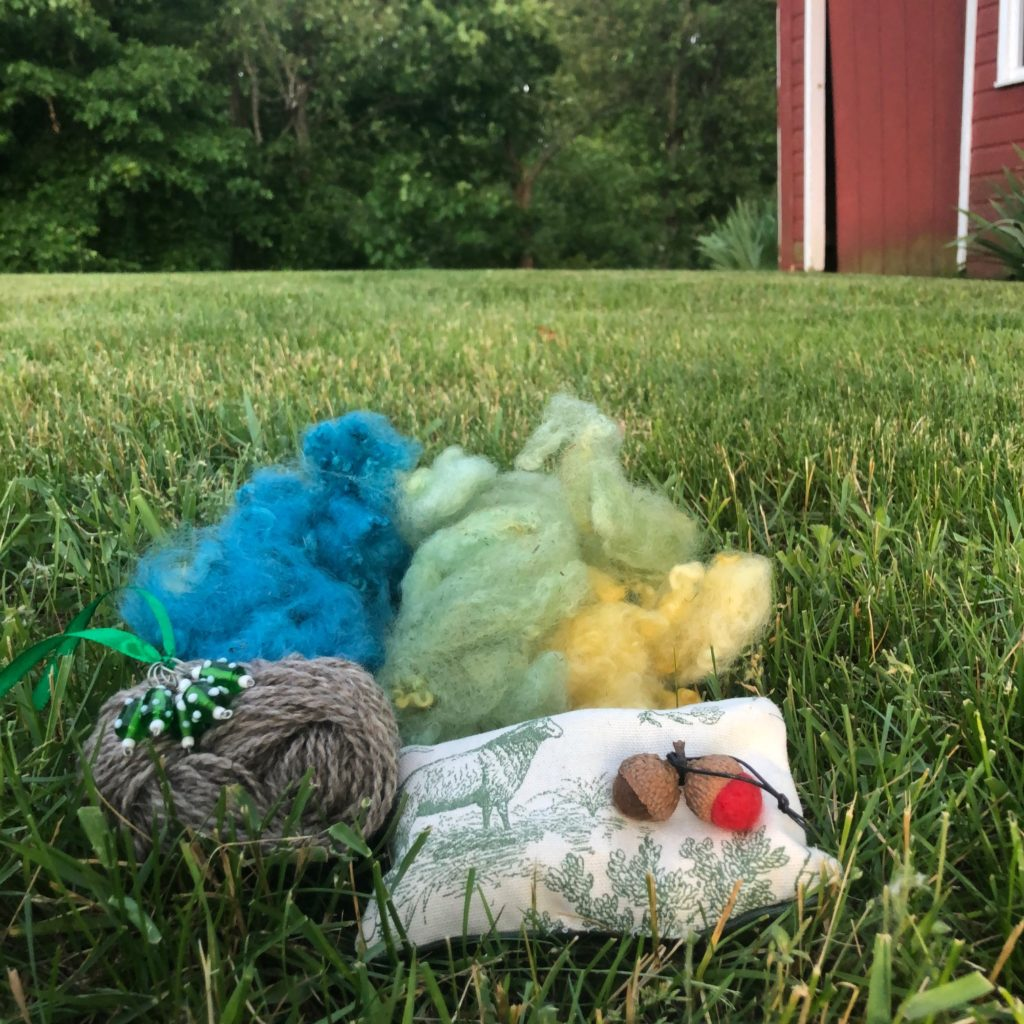 Blue, green, and yellow wool, a small hank of brown wool, green stitch markers, a green and white sachet, and red and brown felted acorns sitting in the grass.